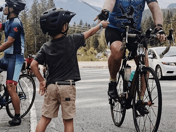Young child handing cookie to cyclist