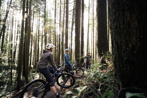 Female mountain bikers on a trail in the woods