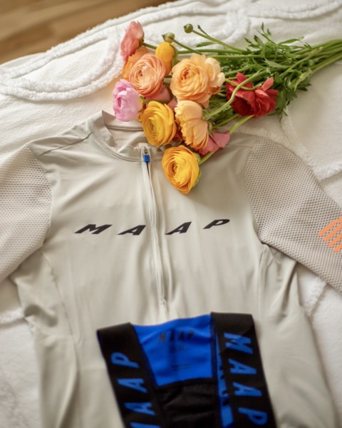 Cycling kit laid out on a bed with a bouquet of flowers
