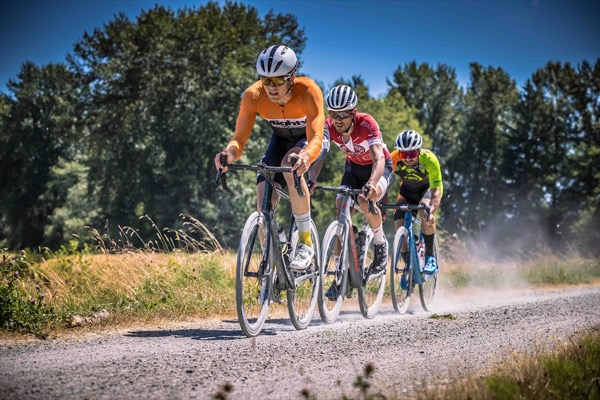Lead break group of three riders riding on gravel path.