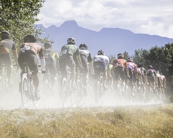 A group of riders in double line formation riding along gravel path with mountain backdrop